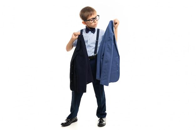 Школьник выбирает между черным и синим пиджаком