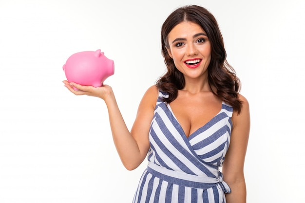 美しい白人女性はピンクのブタ貯金箱と笑顔、白で隔離される画像を保持します