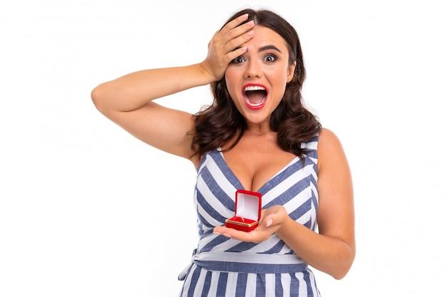 Молодая девушка с восхитительной улыбкой, плоскими зубами, красной помадой, длинными волнистыми каштановыми волосами, красивым макияжем, в бело-голубом платье в полоску с расщеплением держит в руках красную коробочку с кольцом