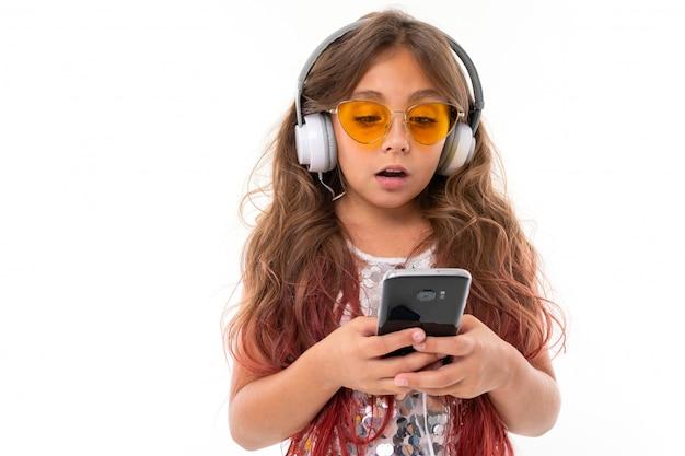 先端のピンク、光沢のある明るいドレス、黒と白のスニーカー、メガネ、ヘッドフォンで立って、携帯電話を手に持って染めた長いブロンドの髪の十代の少女