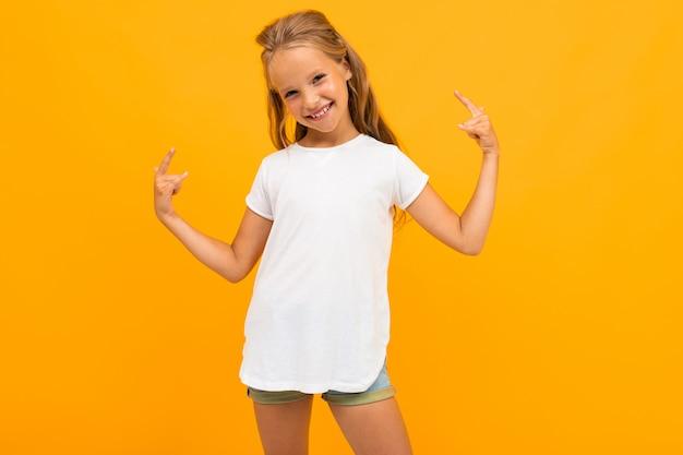 Красивая девушка на желтом смеется в белой футболке