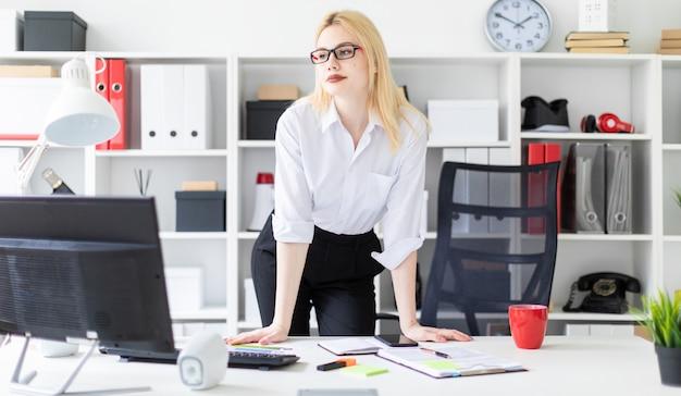 コンピューターのテーブルで事務所に立っている若い女の子。