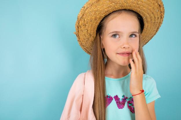 Девочка-подросток с серыми глазами, милой улыбкой и в шляпе на синем фоне