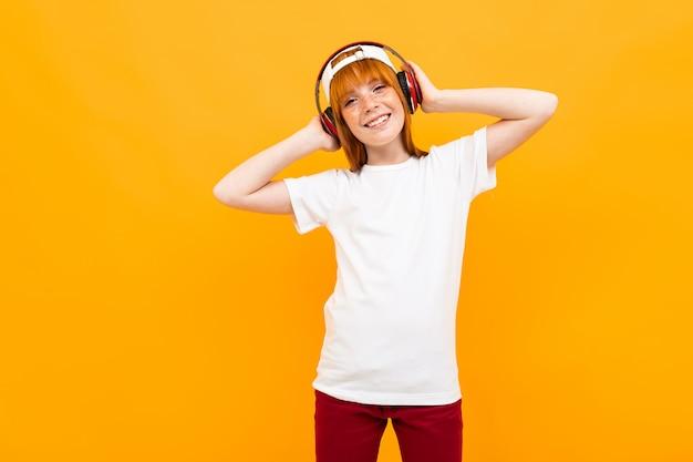 Красивая девушка-подросток европейской внешности на желтом фоне в белой футболке слушает музыку в наушниках