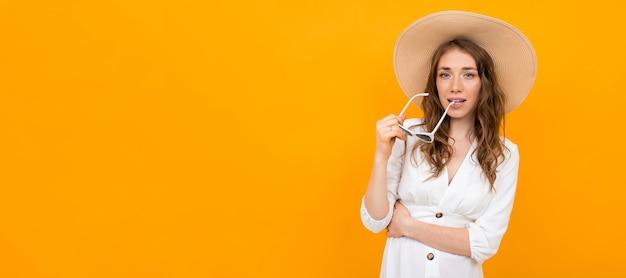 Стильная женщина в шляпе и очках позирует на желтом