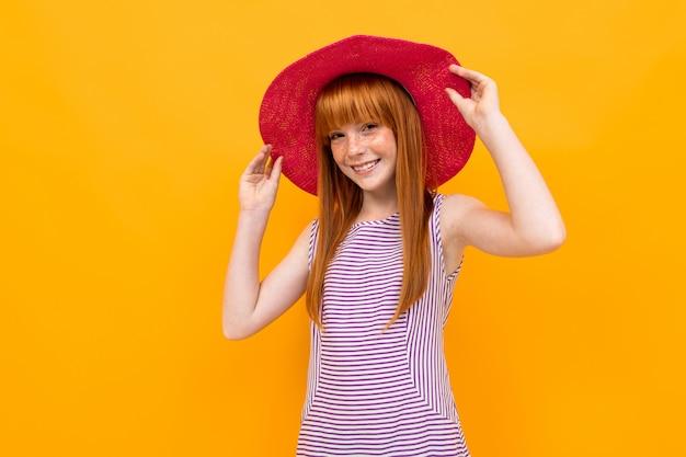 Рыжая молодая девушка в летней красной шляпе