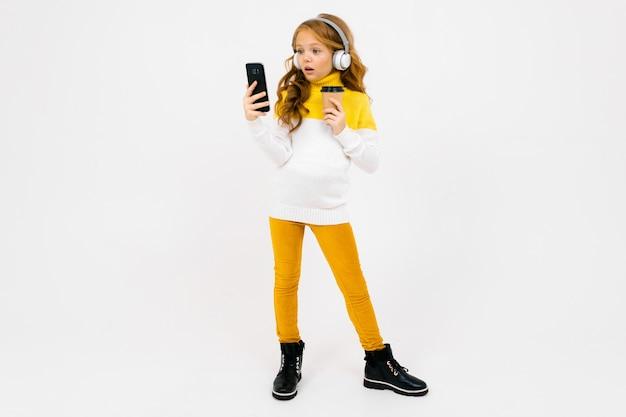 白いヘッドフォンでかわいい若い女の子は、携帯電話を見て、ガラスを保持しています