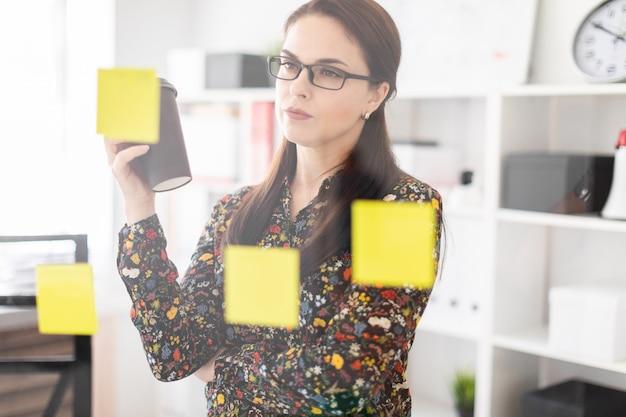 若い女の子がステッカーが付いている透明な板の近くのオフィスに立ちコーヒーを飲みます。