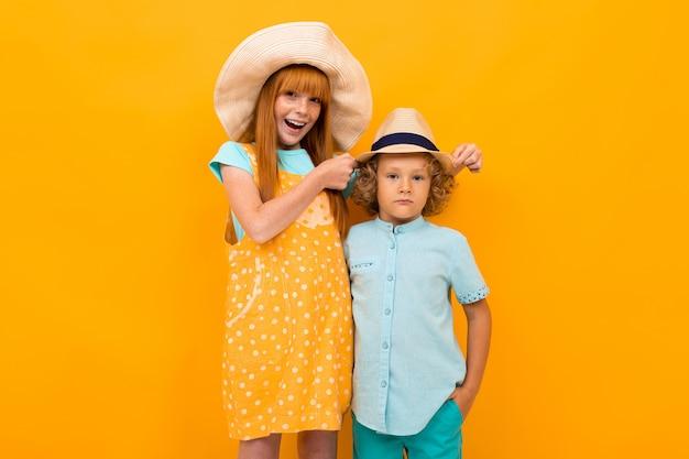Счастливый рыжий мальчик и девочка в летних шляпах