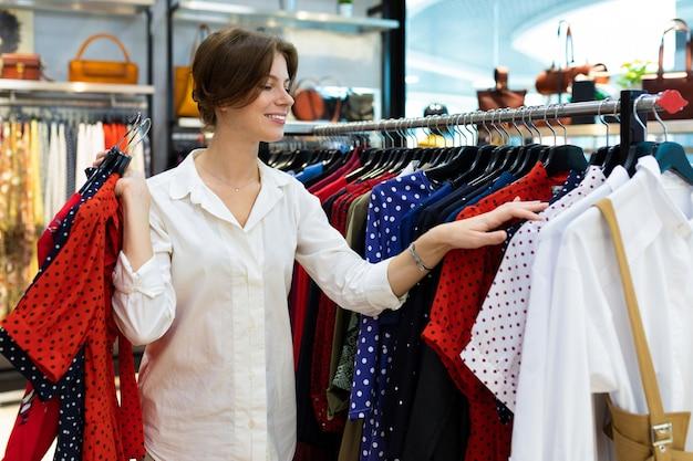 Молодая усмехаясь женщина выбирает платье и держит немногие