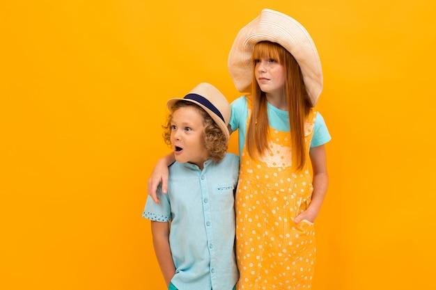 Два удивленных рыжих брата и сестра смотрят в летние шляпы, глядя в сторону