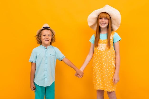 Два рыжеволосых мальчика и девочка в летних шапках держатся за руки