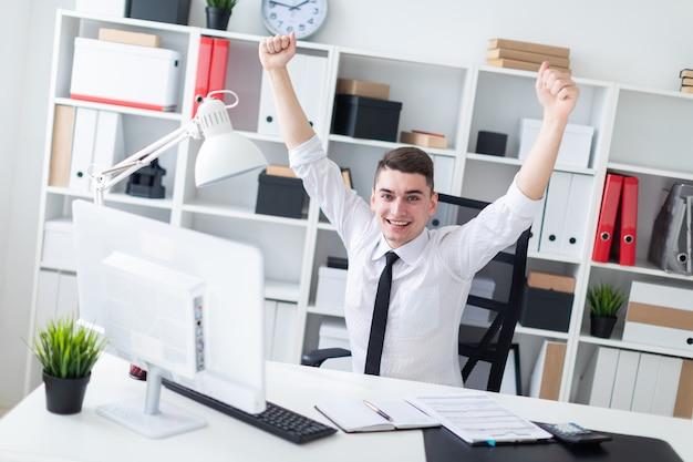 若い男がオフィスのコンピューターの机に座って手を挙げた。