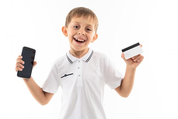 白いシャツを着た少年、ブロンドの髪と青いショートパンツ、携帯電話とカードと黒いメガネが笑っています。