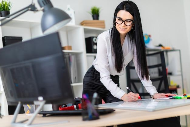 若い女の子がコンピューターの机のそばに立ち、磁気ボードにマーカーを描きます。