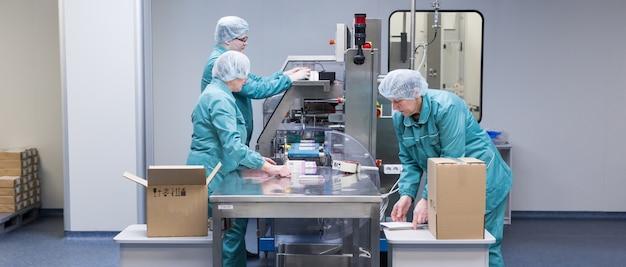 Работники фармацевтического завода в стерильной среде