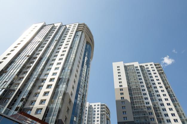 青い空を背景に高いモダンで豪華なタイル張りのアパートの建物の斜めの地面。