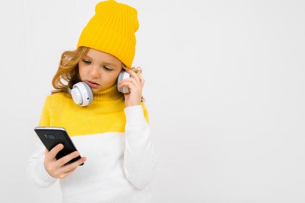Европейская привлекательная девушка читает сообщения на смартфоне с наушниками на ее шее, изолированных на белом фоне