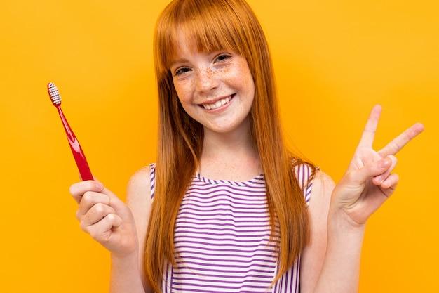 Рыжая улыбающаяся девушка держит зубную щетку в руках на желтом фоне