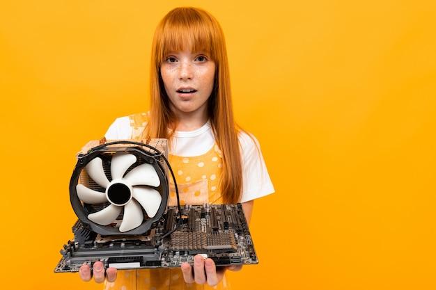 黄色の背景の上のコンピューターからファンを保持している赤い髪の少女