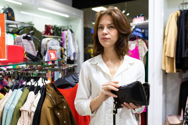 Молодая женщина думает о покупке одежды или новой вещи, стоя в магазине одежды