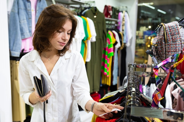 若い女性は洋服店で立っている値札を見てください。
