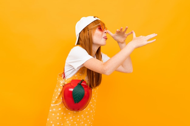 Рыжая девушка в очках и с красным яблоком морщится на камеру на желтом фоне