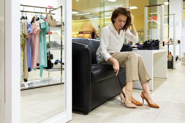 Женщина примеряет кремовую и горчичную обувь в магазине