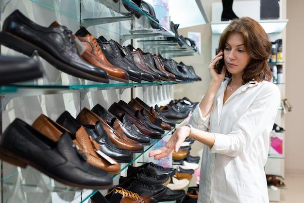 若い白人女性の男性の靴を見て、携帯電話を保持