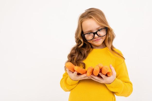 メガネの女の子は、孤立した白い背景にニンジンの果物を保持しています