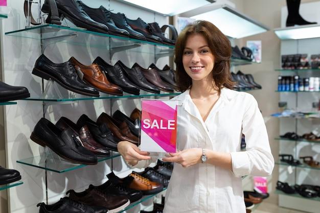 販売とブルネットは、男性の靴の背景に立っている彼女の手でサインインします。