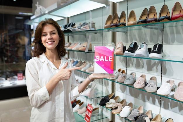 Молодая женщина держит планшет с продажи знак и указывая на него в магазине с обувью женщин