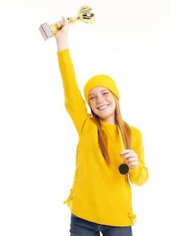 Счастливая рыжеволосая девушка держит чашку и золотую медаль