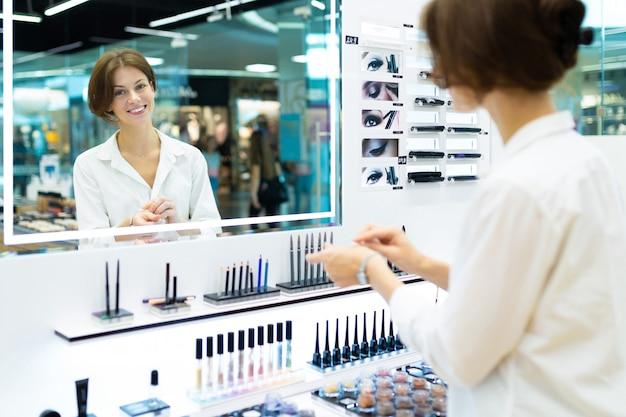 Молодая красивая девушка выбирает свой тональный крем или пудру и улавливает тон кожи перед большим зеркалом