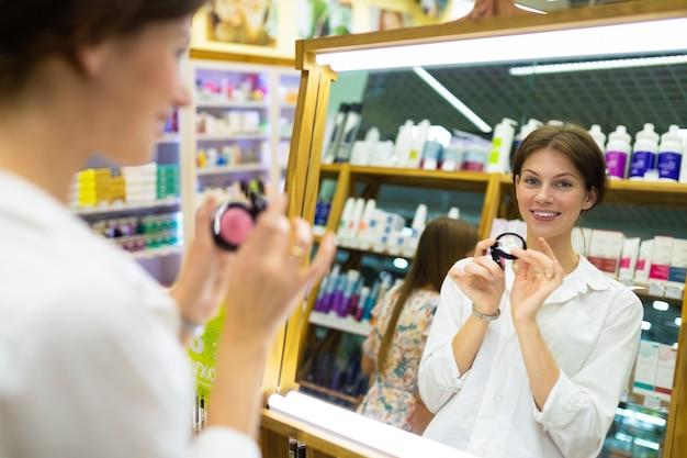 Молодая красивая девушка выбирает свой тональный крем или пудру и улавливает тон кожи перед большим зеркалом и улыбается