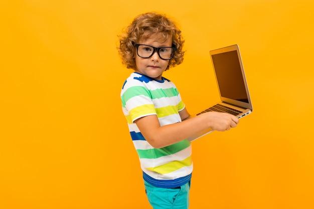 赤い髪の巻き毛の少年は、黄色の背景にラップトップでメッセージを送信します
