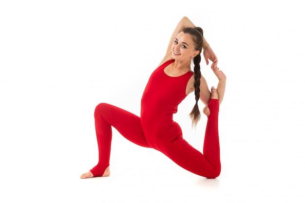赤いスポーツスーツのブルネットの少女は体操