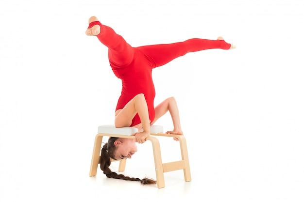 赤いトラックスーツのヨーロッパのブルネットの少女は逆さまの体操を希望