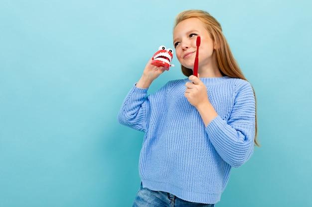Непослушная харизматичная девушка с зубной щеткой на синем фоне, стоматологическая концепция