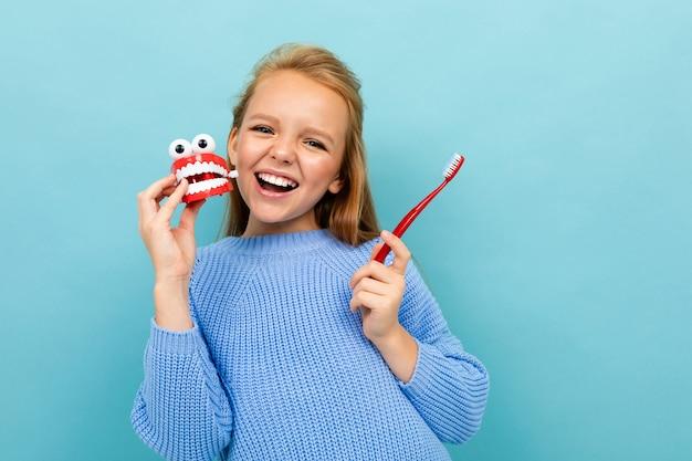 Красивая счастливая девушка смеется на синем фоне с зубной щеткой, концепция зубной пасты