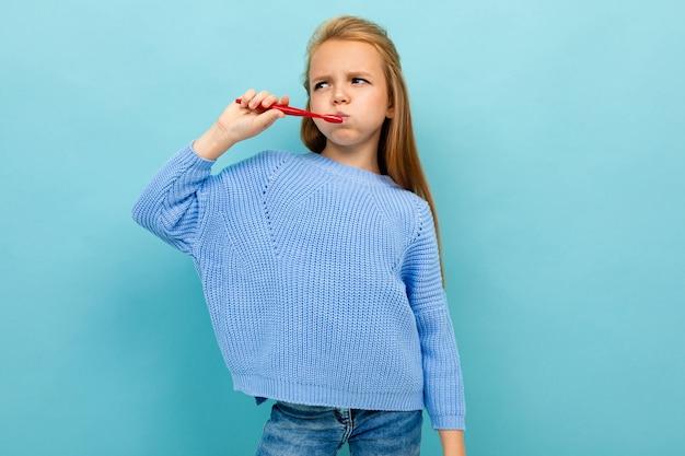 Неудовлетворенная стильная девушка на синем фоне с красной зубной щеткой