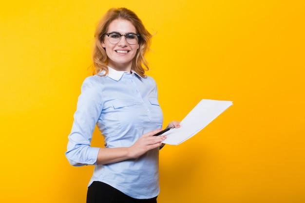 白紙の紙とペンを持つ金髪の女性