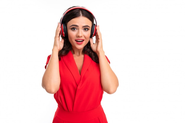 赤い唇を持つ若い女性がヘッドフォンで音楽を聴いて、彼女の口を開く