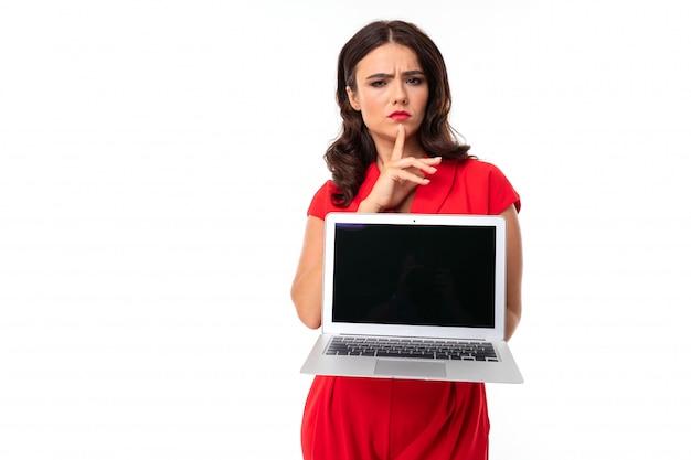 Молодая женщина с красными губами, яркий макияж, работает с белым ноутбуком, думает и показывает что-то на экране, картинка изолирована