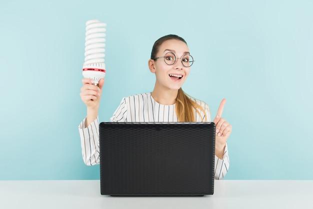 コンピューターと電球を持つ魅力的な女性
