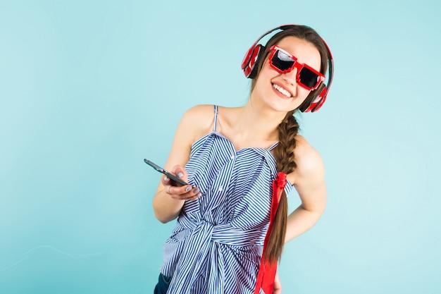 ヘッドフォンと携帯電話を持つ若いセクシーな女性