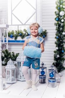 クリスマスツリーの横に立っている笑顔の女の子