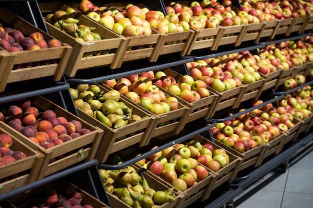 果物がいっぱい入った木製のラグボックス付きのスーパーマーケットカウンター:リンゴ、ナシ、モモ