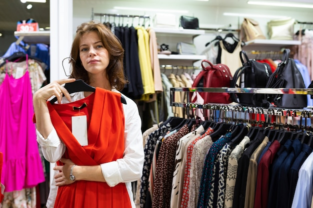 Вдумчивый женщина держит красное платье в магазине одежды