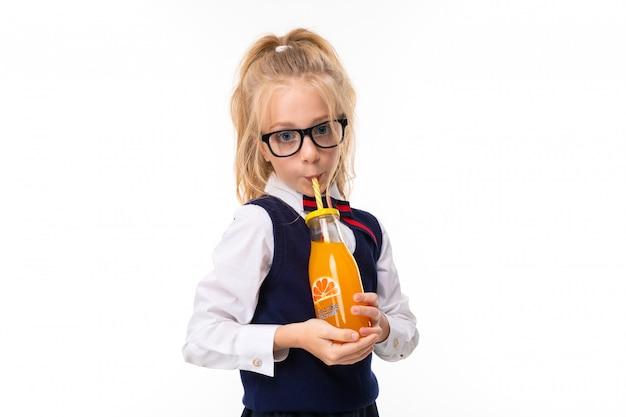 馬の尾に詰められたブロンドの髪の少女、大きな青い目、四角い黒い眼鏡のかわいい顔は、ガラス瓶のチューブにオレンジジュースを飲みます。